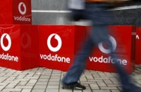 "An Indian man walks past the signboard of telecom firm ""Vodafone"" outside the corporate office in India's financial capital Mumbai. Seven industry bodies from the United States to Japan say an Indian plan to retroactively tax business deals has prompted a widespread review of whether to invest in the country"